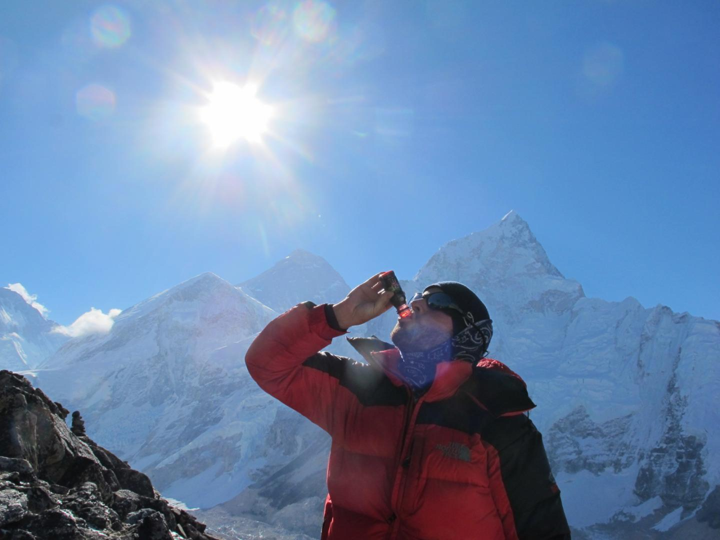 Drinking beet juice can help the human body cope with high altitudes. Here, a study subject drinks beet juice with Mt. Everest in the background. Credit: Harald Engan, Mid Sweden University
