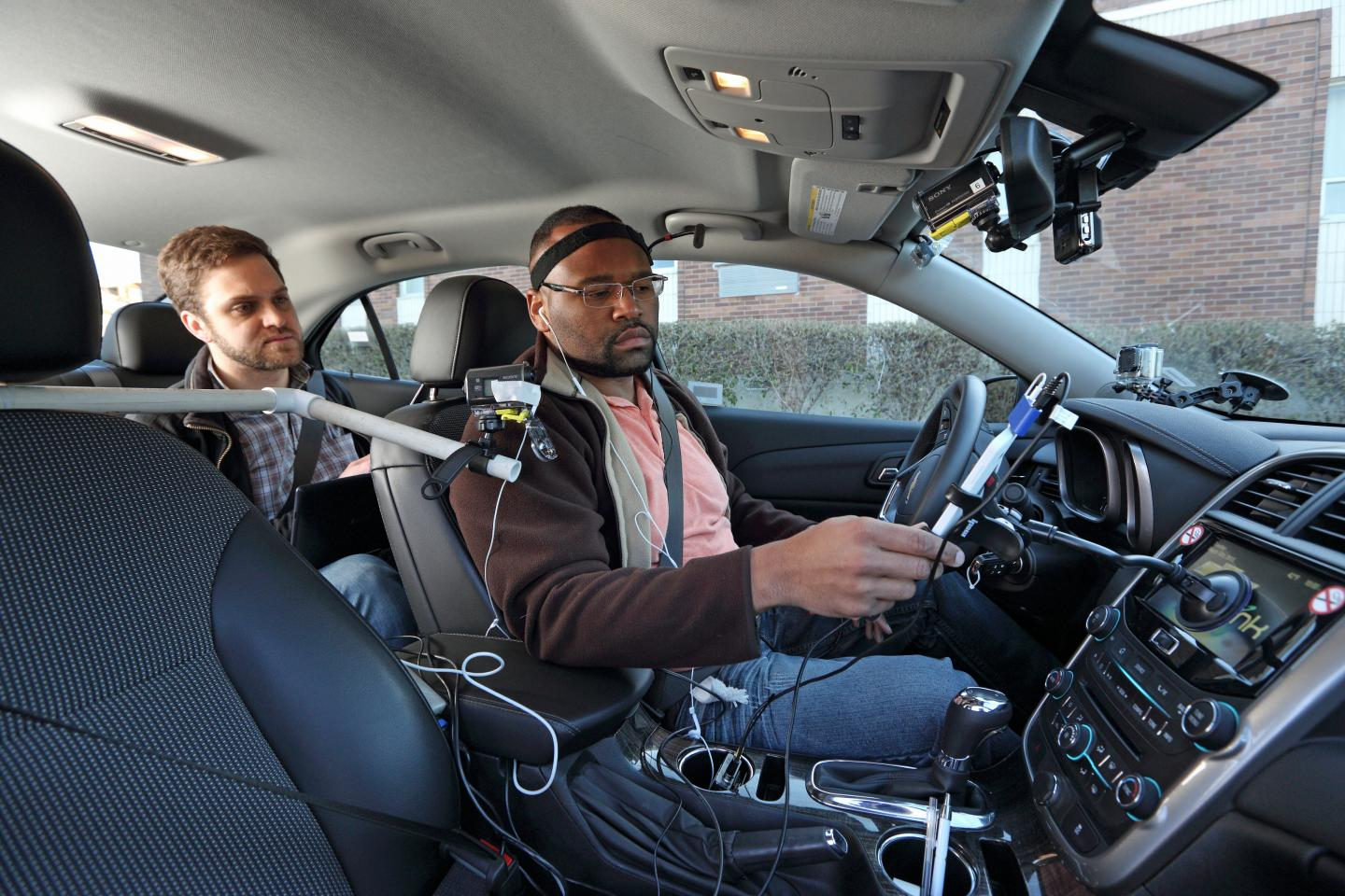 A University of Utah research assistant introduces a participant in new distracted driving studies to special devices designed to gauge mental distraction during road tests. Credit: AAA Foundation for Traffic Safety