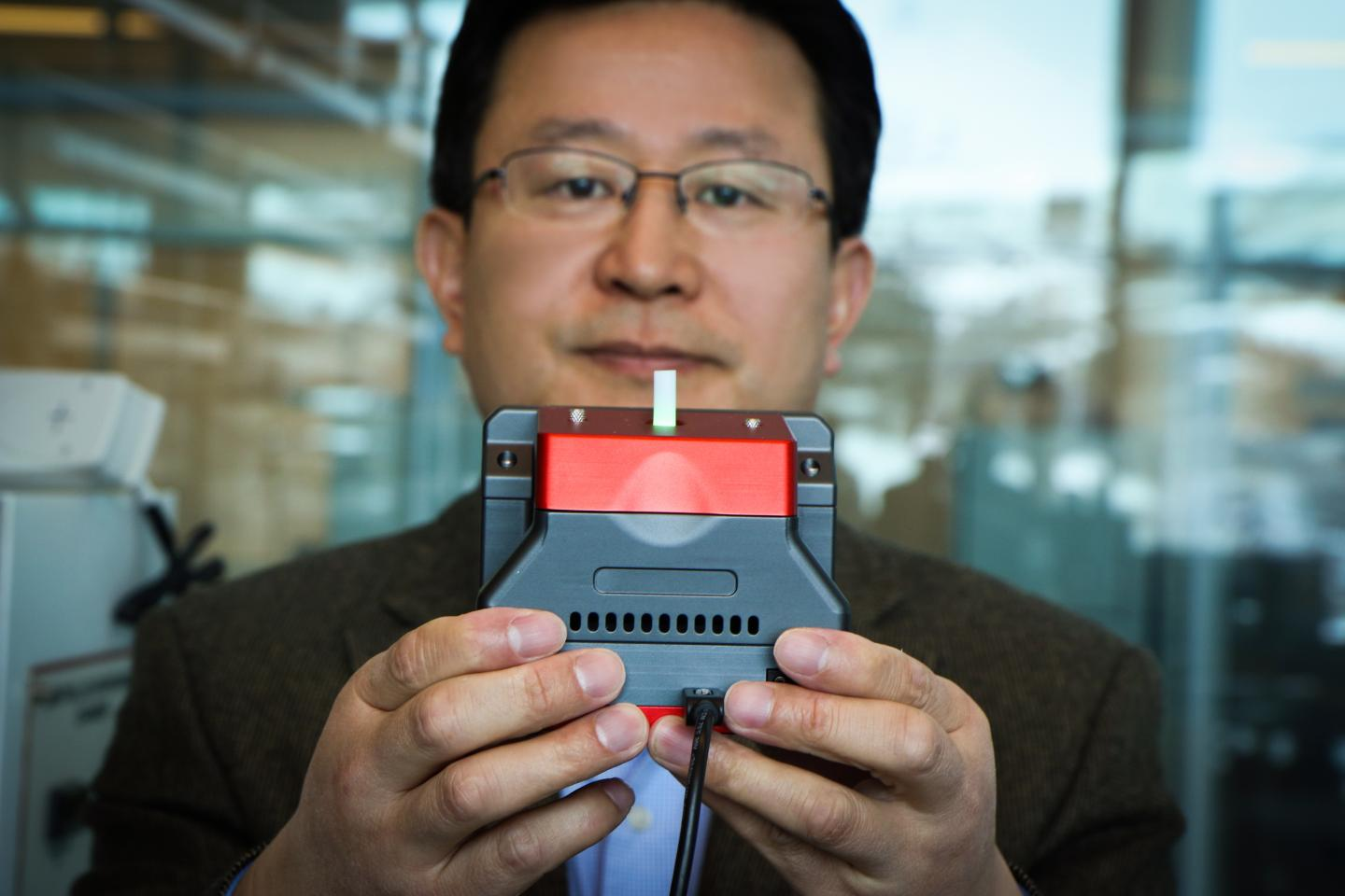 University of Utah materials science and engineering professor Ling Zang holds up a prototype handheld detector his company is producing that can sense explosive materials and toxic gases. Credit: Dan Hixson/University of Utah College of Engineering