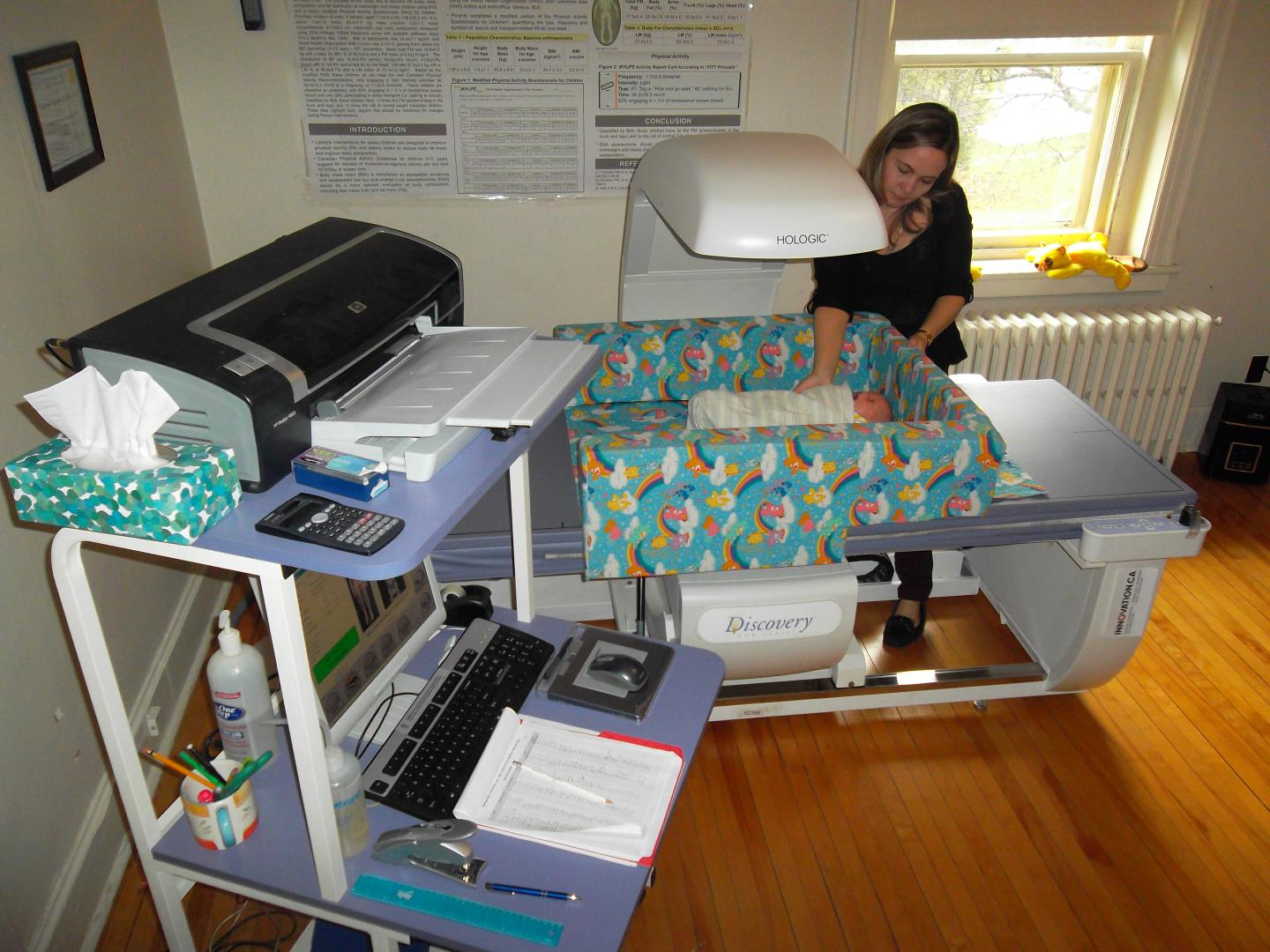 Research nurse setting up the bone densitometer to take an x-ray of an infant's muscle and bone.