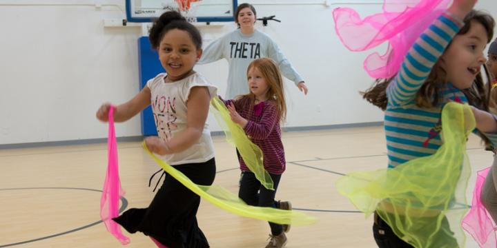 Preschool children at King Street Youth Center in Burlington, Vermont play Chinese Ribbons game with Savanna Salassi and other UVM students as part of a fitness program